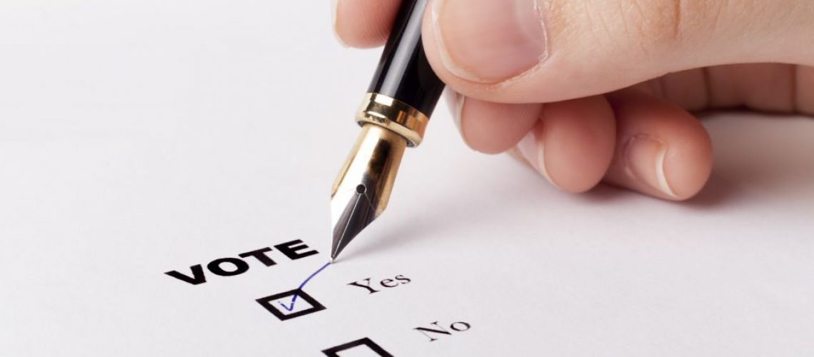 Woman hand voting yes in check-box with blue fountain pen